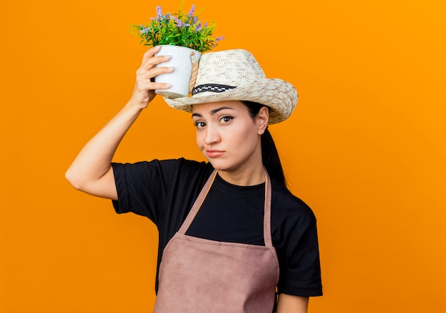 Jeune belle femme jardinier en tablier et chapeau tenant une plante en pot près de sa tête à la mécontentement debout sur un mur orange