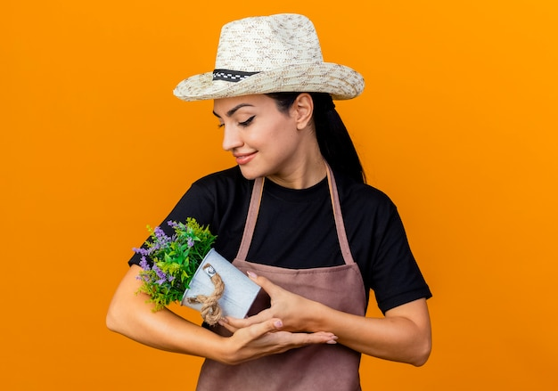 Jeune belle femme jardinier en tablier et chapeau tenant une plante en pot en le regardant avec des émotions positives debout sur un mur orange
