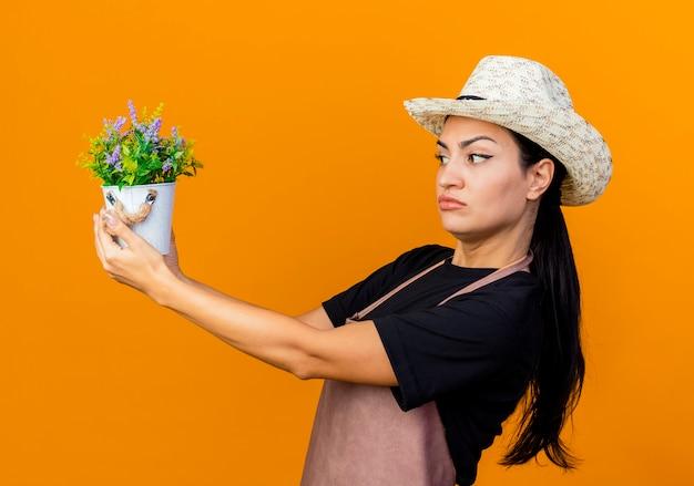 Jeune belle femme jardinier en tablier et chapeau tenant une plante en pot en le regardant avec une expression sceptique debout sur un mur orange