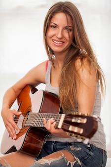 Jeune belle femme jouant de la guitare