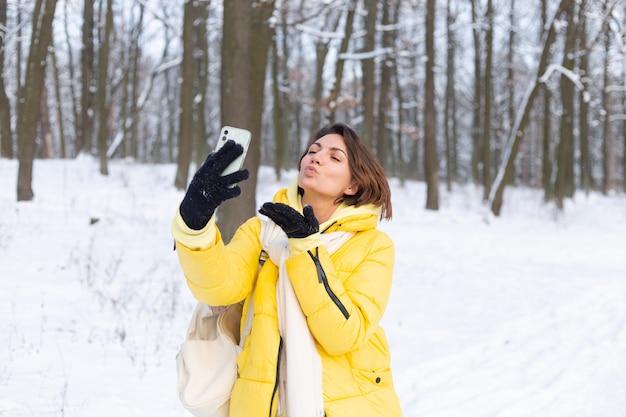 Jeune belle femme joyeuse heureuse dans le blog vidéo de la forêt d'hiver, fait une photo de selfie