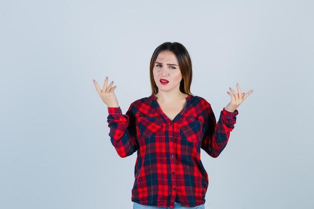 Jeune belle femme levant les mains de manière interrogative en chemise décontractée et l'air furieux, vue de face.