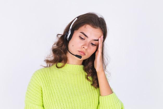 Jeune belle femme avec un maquillage léger de taches de rousseur en pull sur un mur blanc avec un casque d'assistance téléphonique responsable du centre d'appels triste fatigué ennuyé