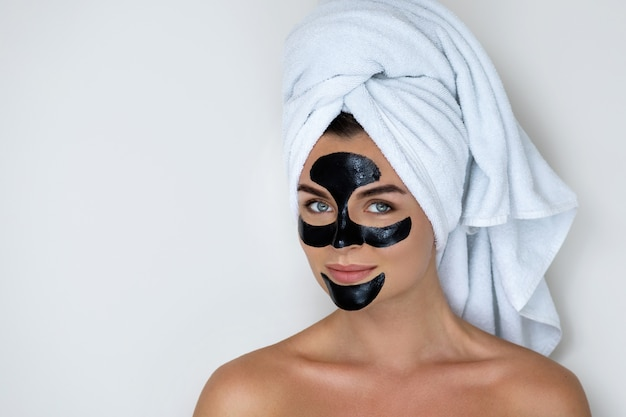 Jeune et belle femme avec un masque peel-off noir sur son visage