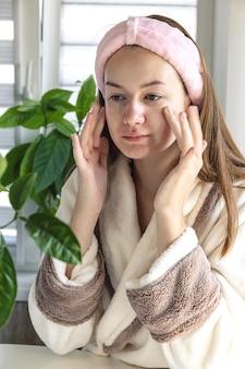 Jeune belle femme avec massage du visage soins de la peau soins personnels appliquant une crème pour le visage