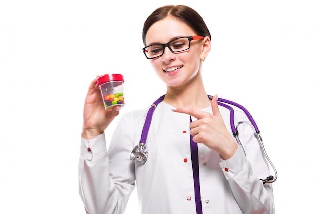 Jeune belle femme médecin tenant une bouteille de pilules dans ses mains sur blanc