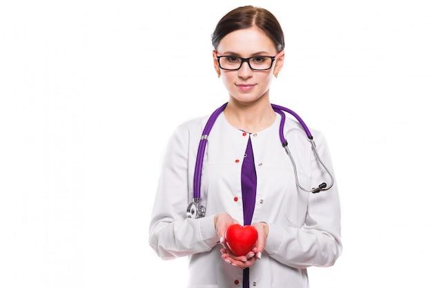 Jeune belle femme médecin tenant coeur dans ses mains sur fond blanc