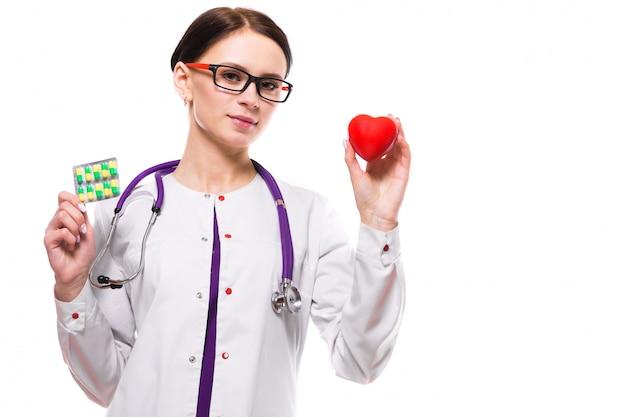 Jeune belle femme médecin tenant coeur et pilules dans ses mains sur blanc