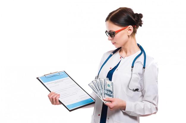 Jeune belle femme médecin tenant le presse-papiers et l'argent dans ses mains sur blanc