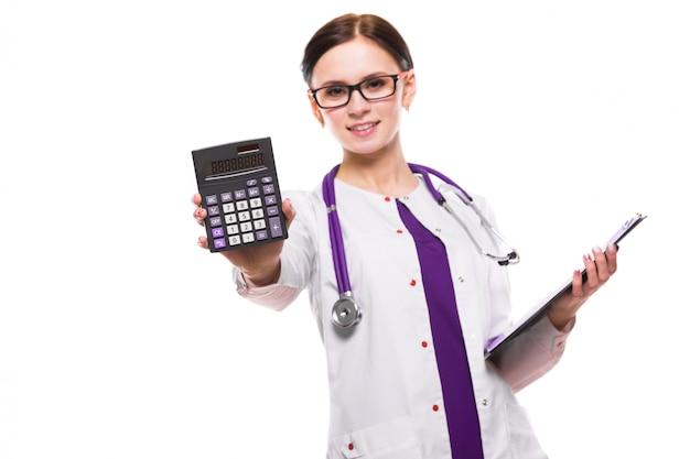 Jeune belle femme médecin tenant presse-papiers et montrant la calculatrice dans ses mains sur blanc