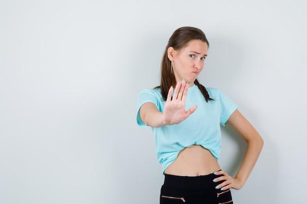 Jeune belle femme montrant un geste d'arrêt en t-shirt et ayant l'air insatisfait. vue de face.