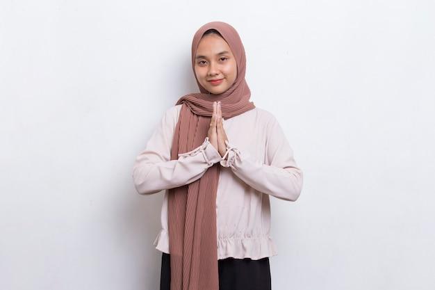 Jeune belle femme musulmane asiatique montre un geste de bienvenue isolé sur fond blanc
