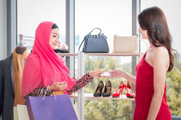Jeune belle femme musulmane a envoyé une carte creadit à des amitiés caucasiennes au magasin de vêtements.