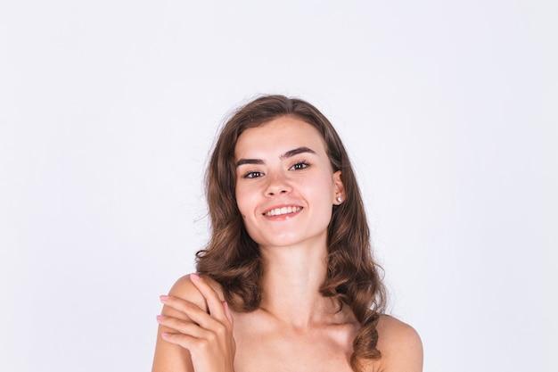 Jeune belle femme naturelle à la peau douce et propre avec un maquillage léger de taches de rousseur sur un mur blanc avec les épaules nues