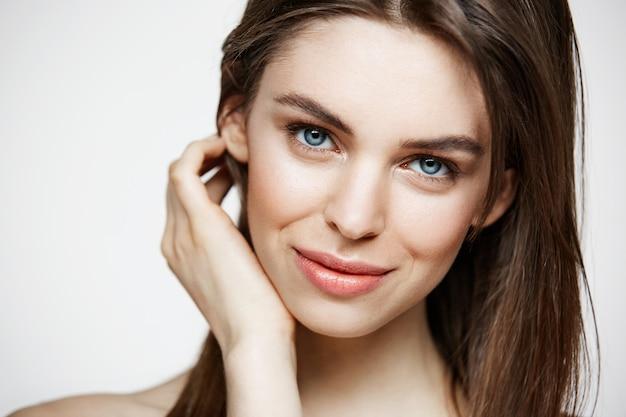 Jeune belle femme nue avec maquillage naturel souriant. cosmétologie et spa. traitement facial.