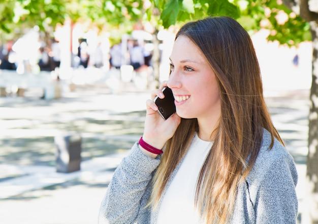 Jeune belle femme parlant au téléphone cellulaire