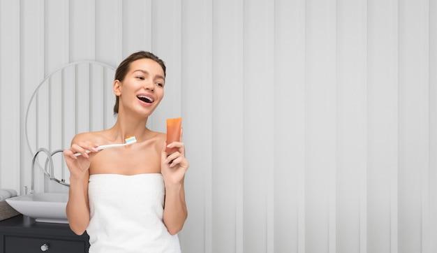 Jeune belle femme sur le point de se laver les dents