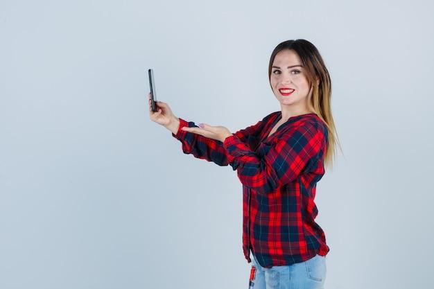 Jeune belle femme prenant un selfie, faisant semblant de tenir quelque chose en chemise décontractée et semblant joyeuse. vue de face.