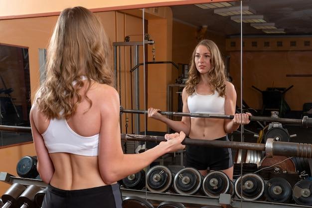Jeune et belle femme regardant dans le miroir et travaillant avec des haltères dans la salle de gym
