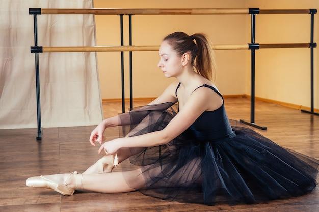 Une jeune et belle femme en robe de ballet attache les pointes à ses pieds. la ballerine s'échauffe dans la classe. la fille de la ballerine dans une belle robe noire.