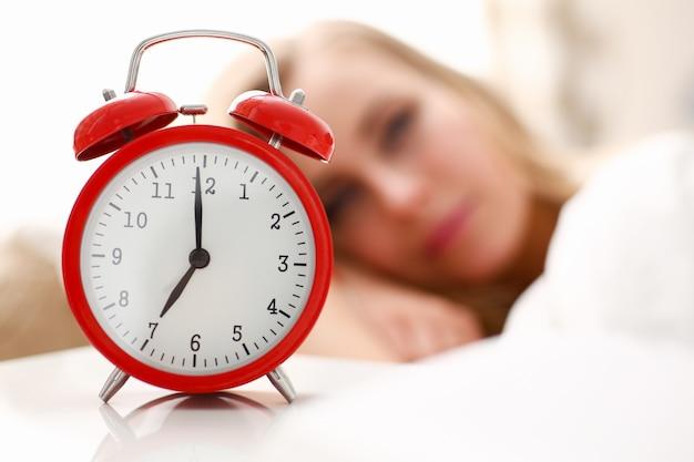 Jeune belle femme se réveillant dans l'alarme du matin