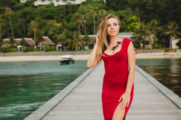 Jeune belle femme séduisante debout seule sur la jetée dans un hôtel de luxe, vacances d'été, robe longue rouge, cheveux blonds, vêtements sexy, plage tropicale, séduisante, sensuelle, souriante