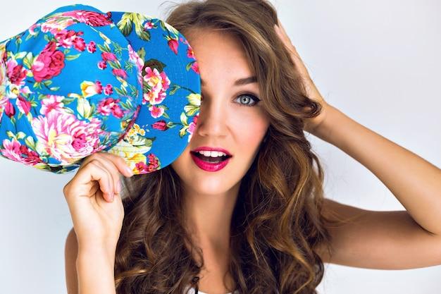 Jeune belle femme sexy chaude ferma son chapeau floral yeux. maquillage lumineux avec des lèvres rouges et de longs cheveux bouclés. émotions surprises.