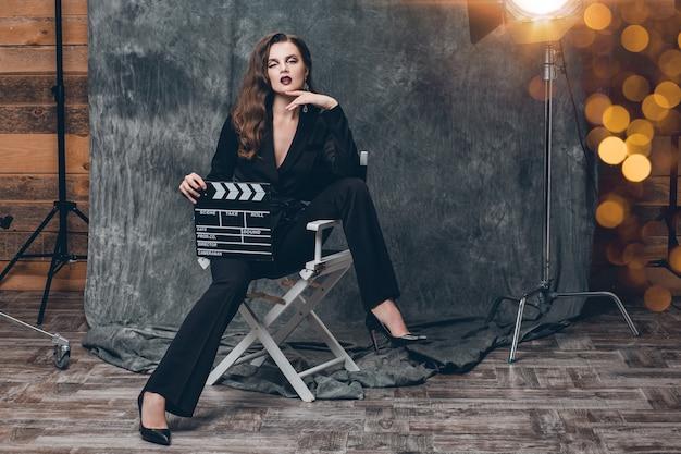 Jeune belle femme sexy élégante sur les coulisses du cinéma, tenant le battant de film