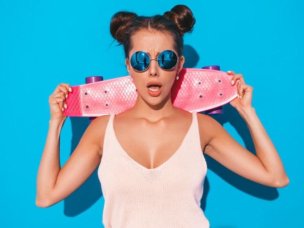 Jeune belle femme sexy hipster souriante à lunettes de soleil.