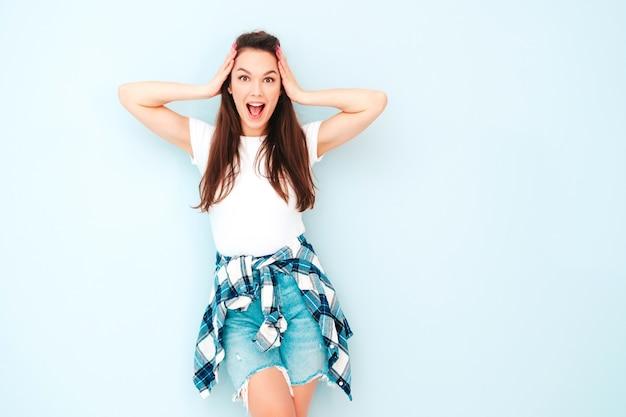 Jeune belle femme souriante dans des vêtements de salopette hipster d'été à la mode