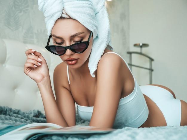 Jeune belle femme souriante en lingerie blanche et serviette sur la tête