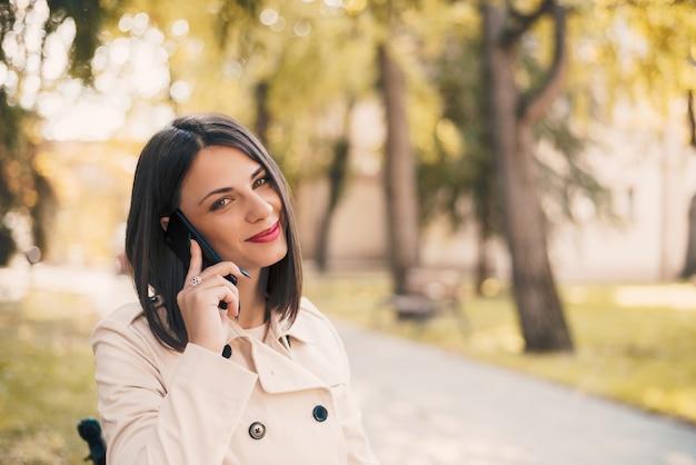 Jeune belle femme souriante parler sur téléphone portable dans le parc.