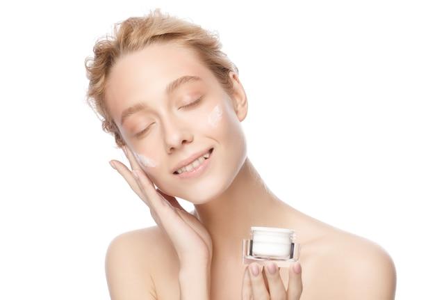 Jeune belle femme souriante à la peau nue tenant un pot cosmétique et appliquant de la crème sur le visage