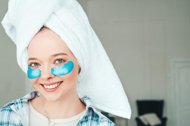 Jeune belle femme souriante avec des taches sous les yeux