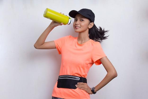Jeune belle femme sportive asiatique buvant de l'eau après l'entraînement sur fond blanc
