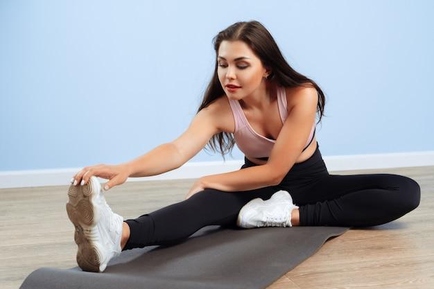 Jeune belle femme sportive faisant des exercices d'étirement sur un sol