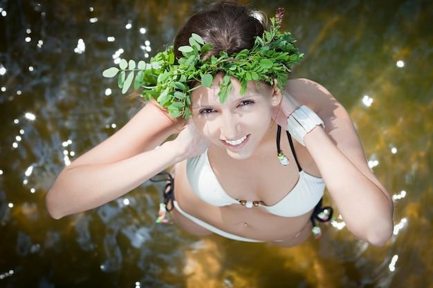 Jeune belle femme t avec une couronne de fougère debout dans l'eau