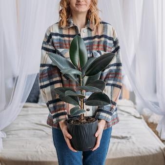 Jeune belle femme tenant le pot, pas de visage. une jolie jeune femme apporte un pot de fleurs vert dans une nouvelle maison. concept d'appartement sans visage ou à louer