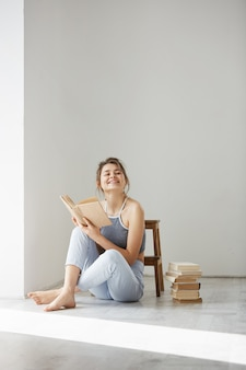 Jeune belle femme tendre souriant tenant un livre assis sur le sol sur un mur blanc tôt le matin.