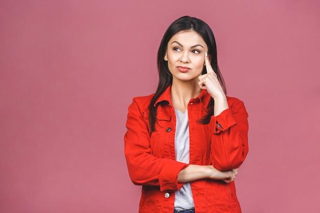 Jeune belle femme triste hispanique sérieuse et inquiète à la recherche d'une expression faciale inquiète et réfléchie déprimée isolée sur un mur rose dans la tristesse et la tristesse