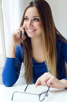 Jeune belle femme utilisant son téléphone mobile à la maison.