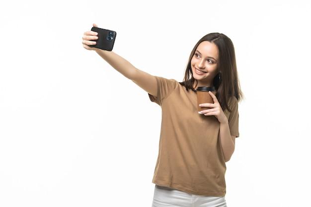 Jeune belle femme utilisant le temps de selfie de smartphone, tenant la tasse de café et le téléphone portable d'isolement sur le blanc
