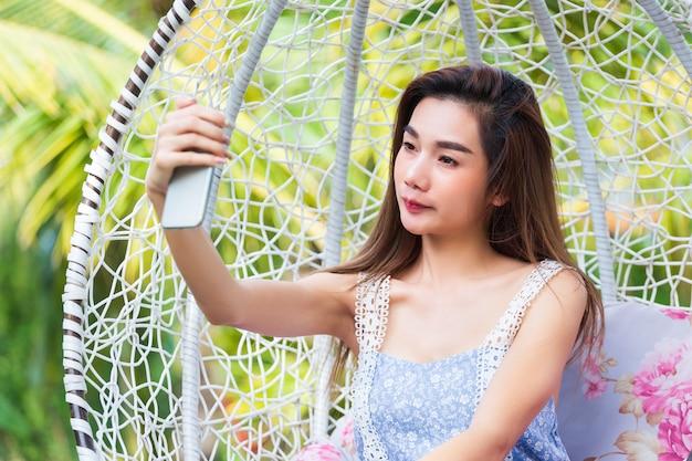 Jeune belle femme utilise smartphoe pour selfie