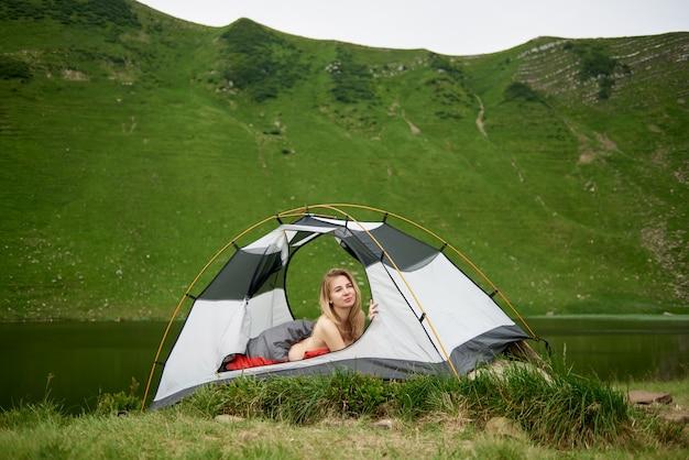 Jeune belle femme voyageur couché dans une tente dans un sac de couchage, belle vue sur le lac dans les montagnes à l'arrière-plan. camping lifestyle concept aventure vacances d'été en plein air