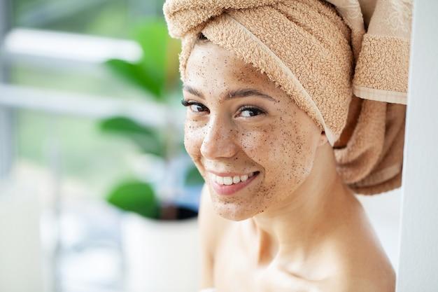 Jeune belle fille appliquant un masque de gommage facial sur la peau.