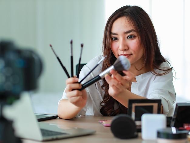 Jeune et belle fille asiatique montre divers pinceaux pour le visage à la caméra avec le sourire et heureuse lors de l'enregistrement vidéo diffusé sur le contenu et l'examen des cosmétiques. concept de vente et de marketing en ligne.