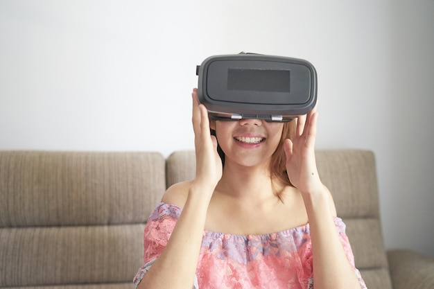 Jeune belle fille d'asie se détendre et s'amuser avec des lunettes de vr sur le canapé à la maison
