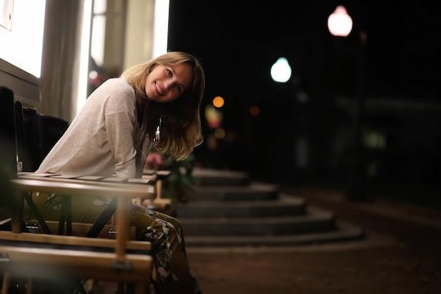 Jeune belle fille assise dans un café de rue la nuit