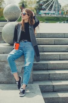 Jeune belle fille assise sur les marches avec du café dans des verres.