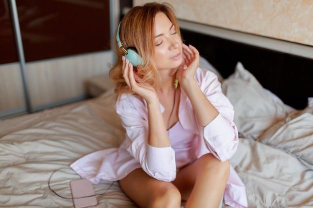 Jeune belle fille au gingembre écoutant de la musique par des écouteurs au lit après le réveil complètement reposé.